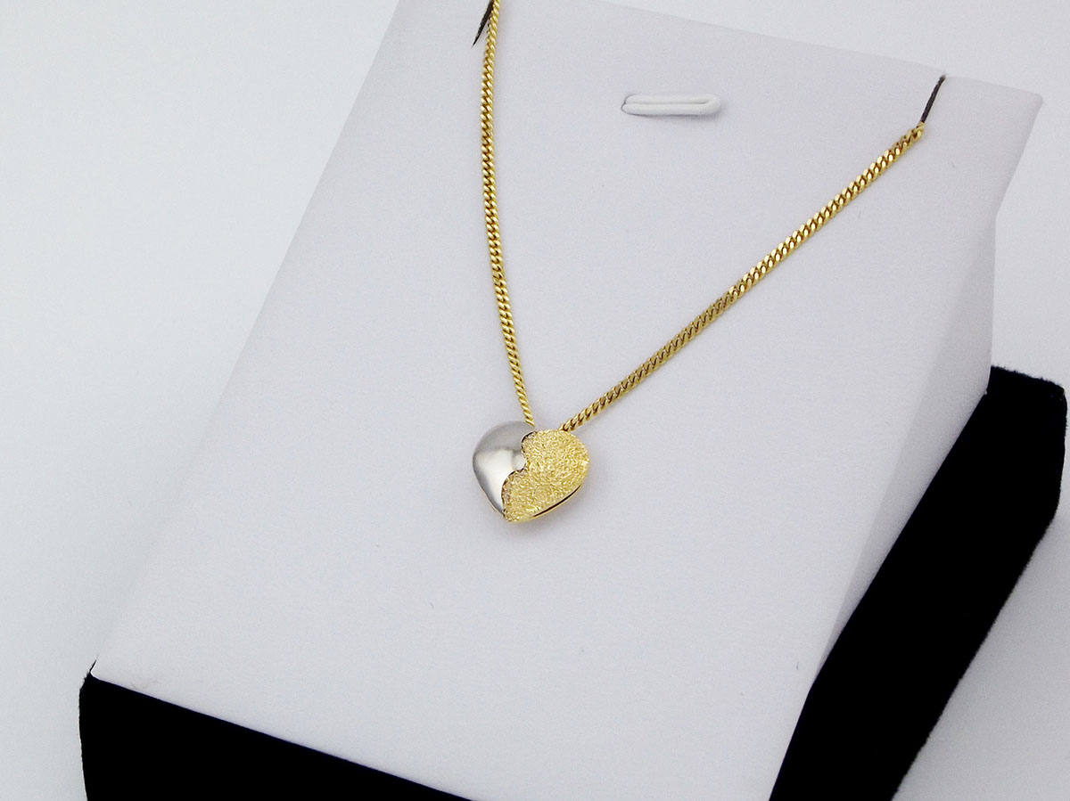 Et todelt hjerte vedhæng i guld og hvidguld
